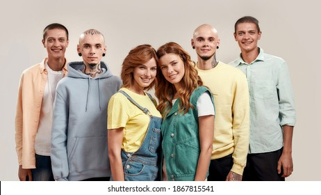 Portrait of young twin brothers and sisters smiling at camera, posing together, standing isolated over light background. Family relationships concept. Front view. Web Banner