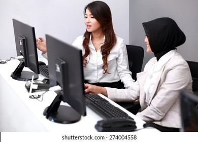 portrait of young two businesswomen discussing their work at office