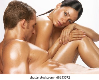 Portrait of a young undressed couple on white background. Portrait of a shaped and healthy young couple after bath-spa.