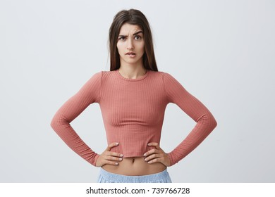 Portrait of young unhappy caucasian girl with dark long hair in trendy pink top and sporty blue trousers looking in camera with angry expression, holding hands on waist, seeing her boyfriend with
