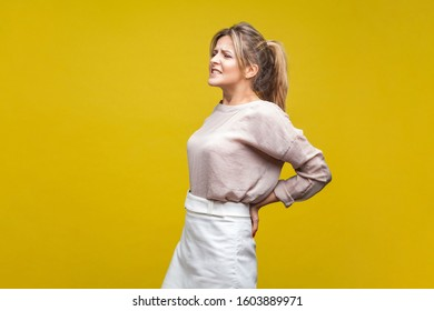 Portrait of young unhealthy woman with fair hair in casual blouse massaging lower back and grimacing in pain, spine problem or kidney inflammation. indoor studio shot isolated on yellow background