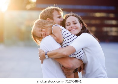 Portrait of a young united family. Father keeps a small daughter in his arms. Woman gently embraces husband and daughter.