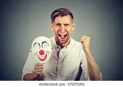 Portrait young upset angry screaming man holding a clown mask expressing cheerfulness happiness isolated on gray wall background. Human emotions feelings
