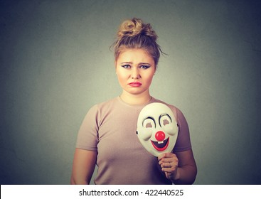 Portrait young upset worried woman with sad expression holding a clown mask expressing cheerfulness happiness isolated on gray wall background. Human emotions