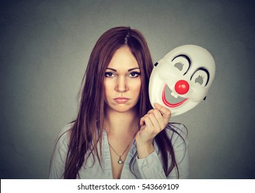 Portrait young upset worried woman with sad expression taking off clown mask expressing cheerfulness happiness isolated on gray wall background