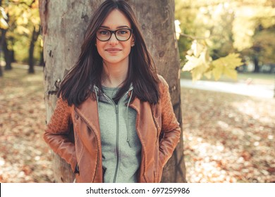 Portrait of young urban style woman standing at park.Autumn season.