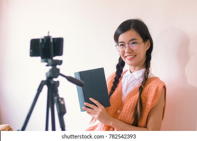 Portrait of Young Vlogger Asian woman filming book review