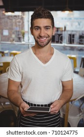 Portrait of young waiter holding digital tablet in cafe
