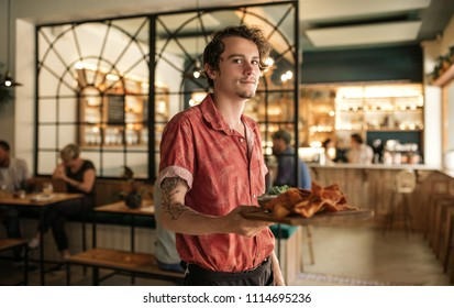 Portrait of a young waiter standing in a trendy bistro full of customers holding an order of freshly baked nachos