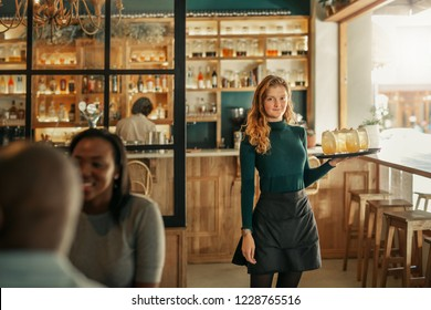 Portrait of a young waitress standing in a trendy bistro full of customers carrying a tray of cocktails