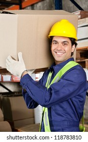 Portrait of a young warehouse worker carrying cardboard box
