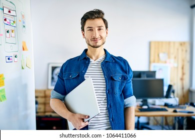 Portrait of young web developer in office holding laptop and looking at notes