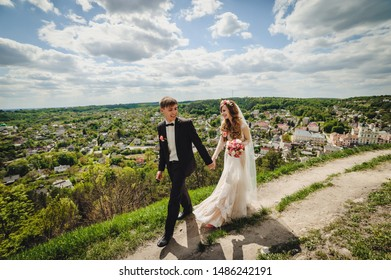 Portrait of young wedding couple are walking country and admire nature and look at the landscape. Wedding ceremony and photo shoot outdoors. Newlyweds.