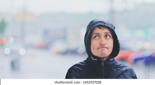 Portrait of a young wet man in a jacket with a hood in the rain on blurred background city street in tsunami, close-up. Bad weather pessimism concept, cold autumn unhappy irony people in raincoat