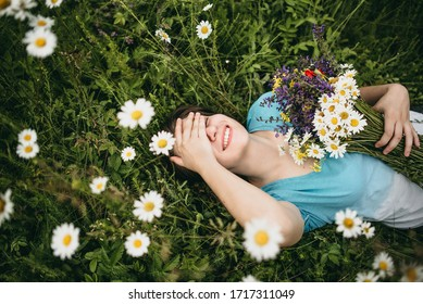Portrait of a young white beautiful woman in a blue T-shirt and no makeup with a bouquet of fresh wildflowers and and a wreath on her head lying on green grass in the summer nature in the mountains.