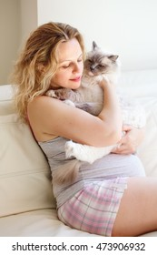 Portrait of young white Caucasian blonde pregnant woman with long hair in tshirt and shorts relaxing at home on  couch holding cat, healthy maternity lifestyle concept