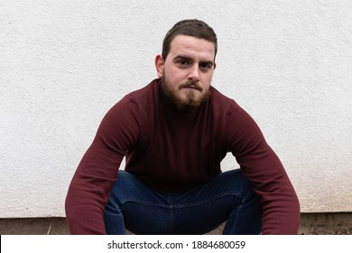 Portrait of young white man wearing dark red shirt while standing in front of isolated white wall posing while crouching.