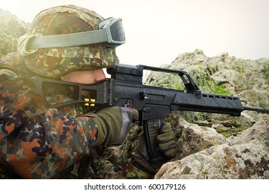 Portrait of young white soldier shooting with automatic rifle gun outdoor.Armed strong military man shoot with firearm weapon on sight.National guard,border patrol protecting the borders with guns