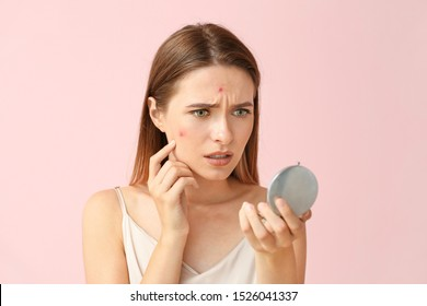 Portrait of young woman with acne problem looking in mirror on color background