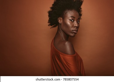 Portrait of young woman with afro hairstyle standing against brown background. African female model looking at camera.