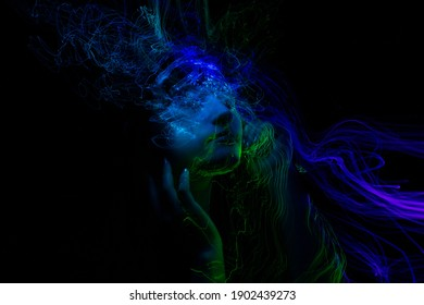 Portrait of young woman amid light painting , Over Black Background. Long exposure photo, light drawing at long exposure