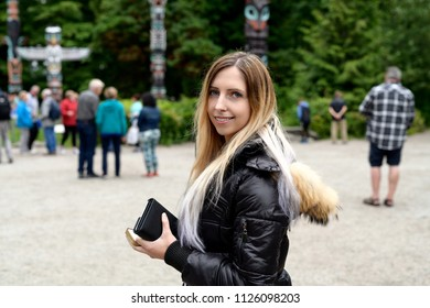 Portrait of a young woman among tourist at Totem poles in Stanley Park, Vancouver, British Columbia, Canada
