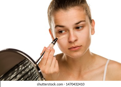 Portrait of young woman applying concealer with brush on white background