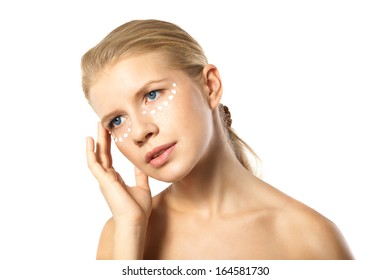 Portrait of young woman applying moisturizer cream on clean fresh face isolated