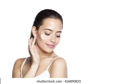 Portrait of young woman applying moisturizer cream on her pretty face. Isolated on white background