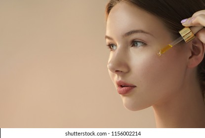 portrait of young woman applying serum on her face on beige background