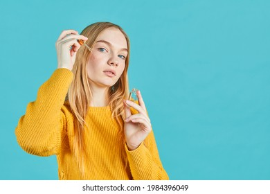 portrait of young woman applying serum on her face on blue background. Teens skin problems.