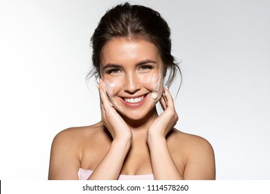 Portrait of young woman applying white foam for washing. Cheerful brunette with perfect clean skin looking at camera with gladness. Skincare spa relax concept. Isolated on grey background