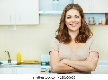 Portrait of young woman with arms crossed standing against kitchen interior background.