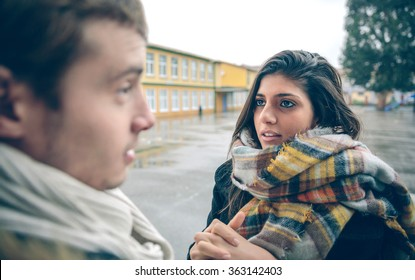 Portrait of young woman asking apologize to offended man after a hard quarrel outdoors. Couple relationships and problems concept.