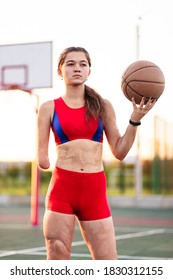 Portrait young woman athlete with an amputated arm and burns on her body. She hold in the hands basketball ball after training outdoor at sunset.