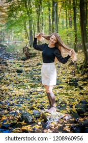 Portrait of young woman in Autumn in forest with falling leaves around. Autumn season