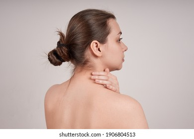 Portrait of a young woman from the back with bare shoulders, touching her neck. Isolate on gray background