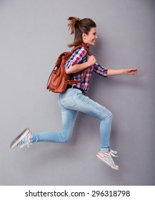 Portrait of a young woman with backpack running over gray background