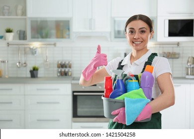 Portrait of young woman with basin of detergents in kitchen. Cleaning service