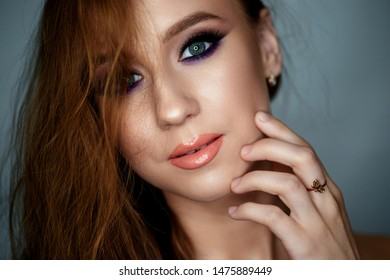 Portrait of a young woman with beautiful evening make-up on a dark background