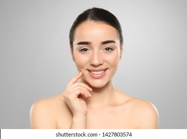 Portrait of young woman with beautiful face against color background
