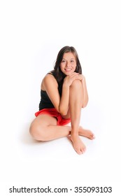 Portrait of a young woman with a beautiful smiling face, she's wearing red shorts and black top sitting in front of white studio background