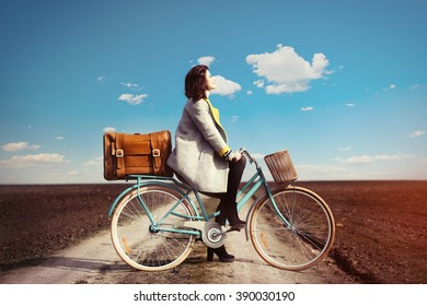 portrait of a young woman with a bicycle and suitcase standing in the middle of the field
