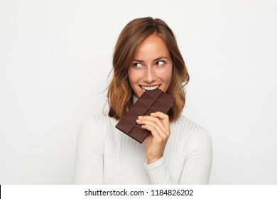 portrait of young woman bites in chocolate looks in camera