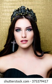 Portrait of young woman with black cross earring and crown, bright make up