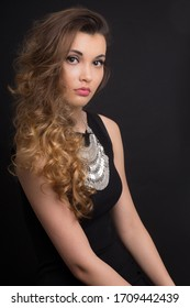 Portrait of a young woman in a black dress with curly hair on a dark background in the studio