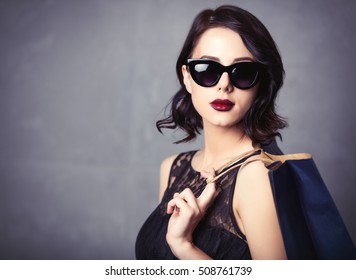 Portrait of young woman in black dress with shopping bag waiting for Black Friday over grey background
