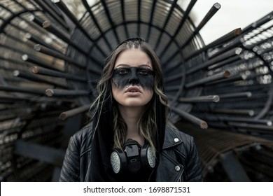 Portrait of young woman with black respirator looking at camera