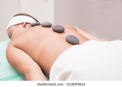 Portrait of a young woman blissfully enjoying spa therapy. close-up. Massage stones