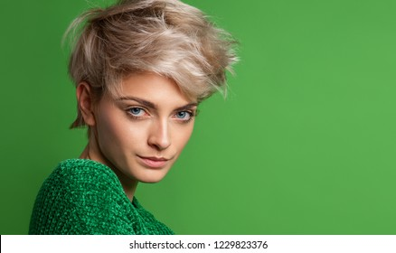 Portrait of young woman with blond short hair isoalted on green background